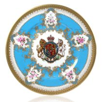 Royal coat of arms fine bone china side plate featuring a lion and unicorn royal crest surrounded by ornated gold patterns and flower patterns on a turquoise blue  background. Gold plated with the words Buckingham Palace, Windsor Castle and Palace of Holy