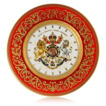 The official commemorative Coronation English fine bone china side plate with a design featuring a royal coat of arms cicled by gold ornamental features on a red background border.
