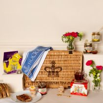 Buckingham Palace hamper surrounded by its contents. Including two boxes of tea, a jar of honey, a jar of jam, a jar of marmalade, two wooden egg cups, gold spoons, and a blue tea towel. Props include vases of flowers and cups of tea and slices of toast.