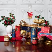 Against a white panel background stands a brown wicker hamper with a blue lining printed with a gold crown and the words 'Buckingham Palace.' To the left of the hamper is a white vase with holly and berries. In front of this is a glass jar of caramel sauc