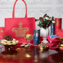 Red Christmas gift crown displaying a gold crown. To the left is a glass stand with a red box of Christmas tea, and a gold dish of mince pies topped with holly and berries. In front of the bag is a glass bowl of chocolate coins and some biscuits are sat n