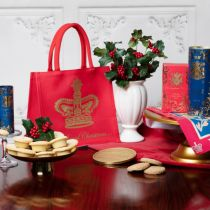 Red Christmas bag next to a white vase of holly and berries. To the left is a blue tube of shortbreads and a gold plate of mince pies. There is a gold foiled chocolate coin in front of the bag and some biscuits. To the right is a gold cake sand with a red