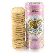 pink biscuit tin with the crest at the centre of the tin. Stood next to a tower of strawberry biscuits