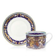 The longest reigning monarch teacup and saucer. The saucer is stood behind the cup. With a white centre and a purple, gold and light blue edge. The cup is purple, light blue and gold with the lion and unicorn crest at the centre.