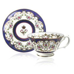 Queen Victoria teacup and saucer with design featuring Queen Victoria's name cipher surrounded by floral patterns and gold plated rim.