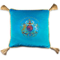 Buckingham Palace blue velvet cushion featuring an embroidered royal coat of arms surmounted by the words God Save The Queen, golden rope rims and tassels in each corner.