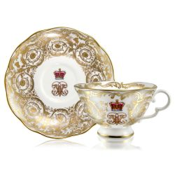 Victoria and Albert teacup and saucer featuring the ciphers of Queen Victoria and Prince Albert surmounted by a royal crown and surrounded by intricately ornated gold patterns and gilded rims.
