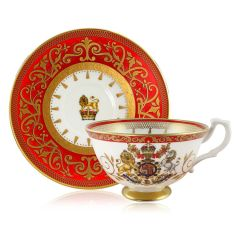The official commemorative Coronation English fine bone china teacup and saucer with a design featuring a royal coat of arms circled by gold ornamental features on a red background border.