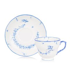White teacup and saucer with a blue floral garland and  bird design
