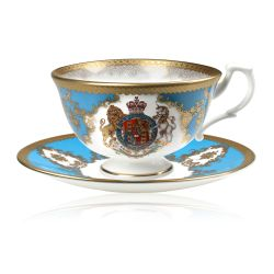 Royal coat of arms fine bone china teacup and saucer featuring a gold rims and a lion and unicorn royal crest surrounded by ornated gold patterns and English flower patterns on a turquoise blue background.