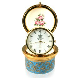 Royal coat of arms fine bone china pillbox clock featuring a lion and unicorn royal crest surrounded by ornated gold patterns and English flower patterns on a turquoise blue coloured background. Integrated pop-up clock on a gold plated hinge and decorated