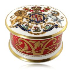 The official commemorative Coronation English fine bone china pillbox with a design featuring a royal coat of arms cicled by gold ornamental features on a red background border.