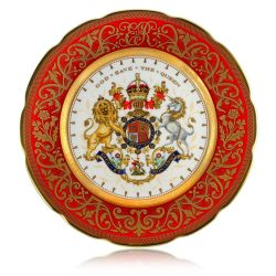 The official commemorative Coronation English fine bone china plate with a design featuring a royal coat of arms cicled by gold ornamental features on a red background border.