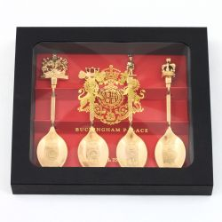 Red and black box of four golden spoons topped with different royal symbols including a crest, crown, guardsman and carriage.