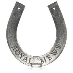 Royal Mews metal horseshoe with the words Buckingham Palace and royal crowns engraved on the back side and Royal Mews engraved on the front side.