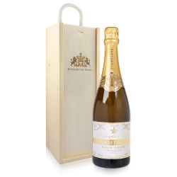 bottle of champagne with gold foil and white and gold  'Buckingham Palace' label next to a wooden bottle box etched with the crest and 'Buckingham Palace'