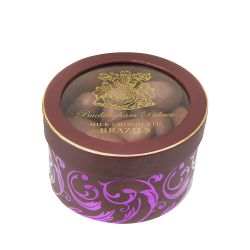 A round chocolate and purple coloured with a clear lid with gold writing stating 'Buckingham Palace Milk Chocolate Brazils'.