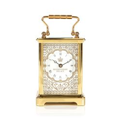 Gold carriage clock with an elaborate pattern and the words 'Buckingham Palace' on the face with a crown.