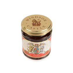 glass jar of strawberry jam with a gold lid. The label is red and white with the unicorn and lion crest