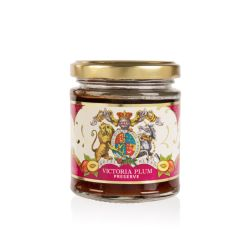 Glass jar of Victoria Plum jam with a gold lid. Wrapped in a purple and white label with the lion and unicorn crest
