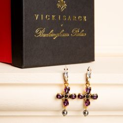 Purple crystal cross drop earrings with a grey faux pearl drop