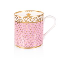 pink patterned coffee mug with a gold design and white handle