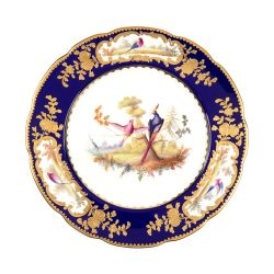 The Sevres plate with two birds painted at the centre and a cobalt blue surrounding. Finished with gold floral motifs.