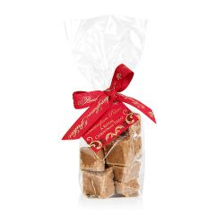 Christmas spiced fudge in a clear plastic bag with a red ribbon stating 'Buckingham Palace' in gold writing.