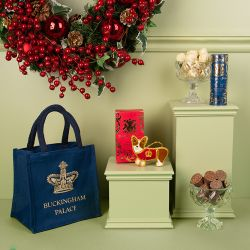 navy juco bag with the words 'Buckingham Palace ' and a crown printed in gold. Two bowls of chocolates including white chocolate champagne truffles and mulled wine chocolates. Blue and gold miniature tube of biscuits and a red and gold box of teabags. A f