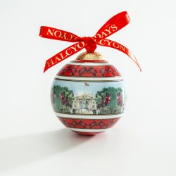 Christmas bauble depicting Buckingham Palace and the Victoria Memorial from The Mall. Including Union Flags and trees down The Mall. Finished with a red bow.
