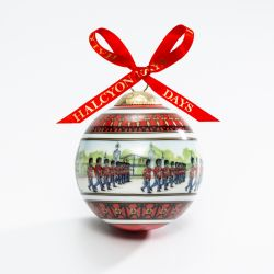 Christmas bauble depicting marching guards in the front court of Buckingham Palace. Finished with a red bow.