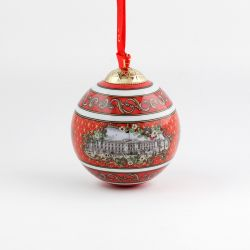 Christmas bauble with red and gold pattern surrounding an illustration of Buckingham Palace