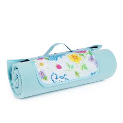 Rolled up blue picnic blanket printed with florals and other royal summertime symbols