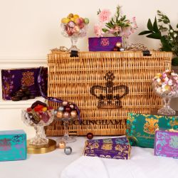Wicker hamper surrounded by boxes of chocolates, bowls of sweets, bowls of marzipan fruits and bars of chocolate