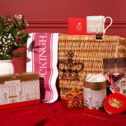 Wicker hamper printed with Buckingham Palace and crown. Surrounded by white vase of flowers, façade tea caddy, façade biscuit tin, red crown decoration and Buckingham Palace postcard pack. On top of the hamper is a façade coffee mug and over one corner of