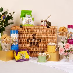 Wicker hamper printed with Buckingham Palace and a crown. Surrounded by a vase of flowers, boxes of green tea and breakfast tea. Salted caramel and chocolate biscuits in a blue tube. Raspberry and white chocolate biscuits in a purple tube. Glass bowls of