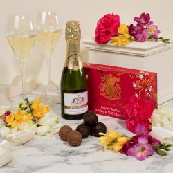 Creative image of miniature champagne bottle next to a pink box of English chocolate truffles. Next to the bottle is two glasses of champagne, some truffles and many colourful flowers