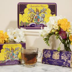 A creative shot of a purple and yellow rectangular biscuit tin on a cream plinth. In front are a yellow and purple box of breakfast tea next to a clear cup of tea and a chocolate bar on the left. White and yellow flowers are amongst the products