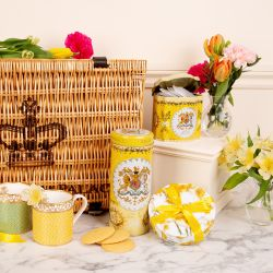 Creative shot of the Buckingham Palace hamper with the yellow lemon biscuit tube at the centre of the shot, the fine bone English china green and yellow mugs to the left and the circular daffodil chocolate box to the right. Behind is a plinth with the yel