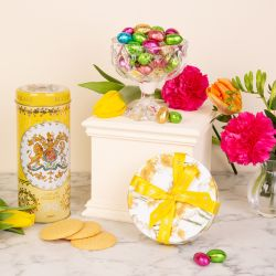 Creative shot of a yellow biscuit tube, a glass bowl of chocolate foiled eggs and a circular chocolate box in a daffodil design. The products are surrounded by colourful flowers.