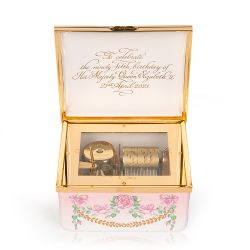 A square music box to celebrate The Queen's 95th Birthday. The lid features a coat of arms and is surrounded by gold borders and a pink roses