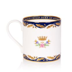White coffee mug with a blue border at the top and bottom with a gold leaf design. At the centre of the mug is Prince Philip's gold cipher.
