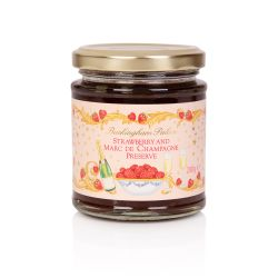 A glass jar of strawberry and champagne jam. On the wrapper, is a garland of strawberries and gold leaves. At the centre are the words 'Buckingham Palace' in gold and 'Strawberry and Marc De Champagne Preserve' in pink. Underneath the writing is a white b