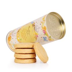 A cardboard tube of orange and lemon biscuits. There is a floral garland at the top and bottom of the tube. At the centre of the tube is an orange oval reading the words 'Buckingham Palace' in gold and 'Orange and lemon shortbread rounds' in orange. The o