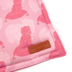 Square pet cushion printed with pink dog printed material with a leather tag saying Buckingham Palace