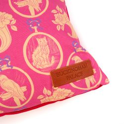Rectangular cushion made with a pink material printed with yellow parrots and cats