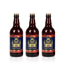 Three glass bottles of ale all wrapped in a blue and red label with gold detail of Prince Philip's cypher.