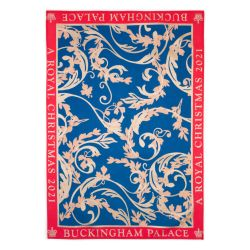 A tea towel with a blue centre featuring a gold design. A red border reads the words 'Buckingham Palace A Royal Christmas 2021'
