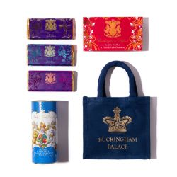 A blue gift bag with a gold crown and the words 'Buckingham Palace' on it is stood on a white cake stand. There is a gold stand of three chocolate bars in purple wrappers. A blue biscuit tube is on the left next to a pink box of chocolates.