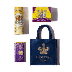 On a mahogany surface, there is a gold tray containing a yellow and purple tea box. A yellow tube of lemon biscuits is stood in a white vase of yellow flowers. There is a blue bag with a gold crown and the words 'Buckingham Palace' stood on a gold cake st